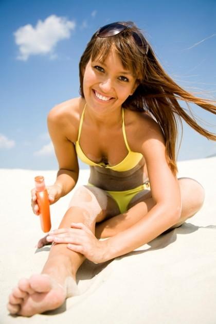 Woman in bikini smears protective cream